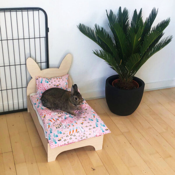 Nini sits on bed with pink rabbit bedding